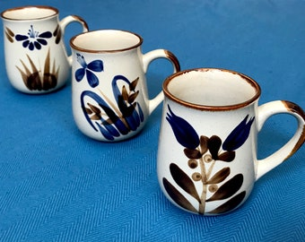 Vintage Stoneware Set Of Three 12 Ounce Mugs, Adorned With Hand Painted Indigo Blue Flowers with Brown Leaves, Handles, and Rims.