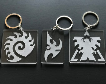 Zerg, Protoss, and Terran Starcraft Faction Keychains on Clear Acrylic