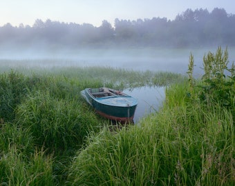Grassy river bank with a boat in the fog