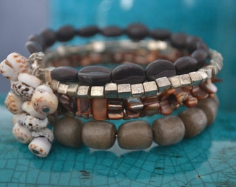 Coffee beans of glass, metal cubes and roccailles, shell hats, pearl pieces and brown seeds and pendants of pukka shell.