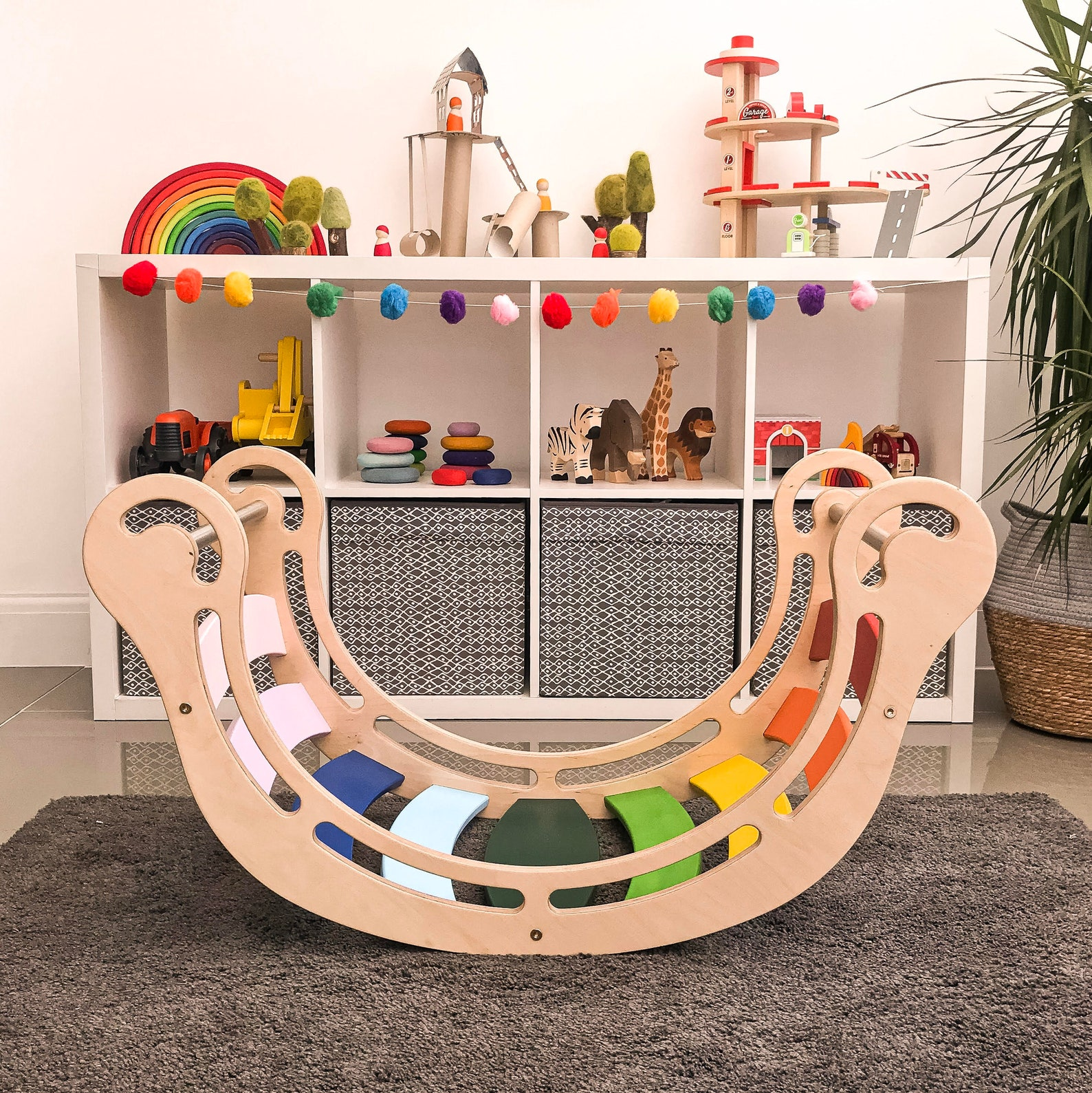 A wooden rocking rainbow on a grey rug in front of toddler shelves featuring wooden toys like a stacking rainbow, wood animals, and staging stones.