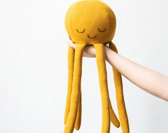 octopus-shaped plush in mustard yellow or gold jersey fabric, limited edition.