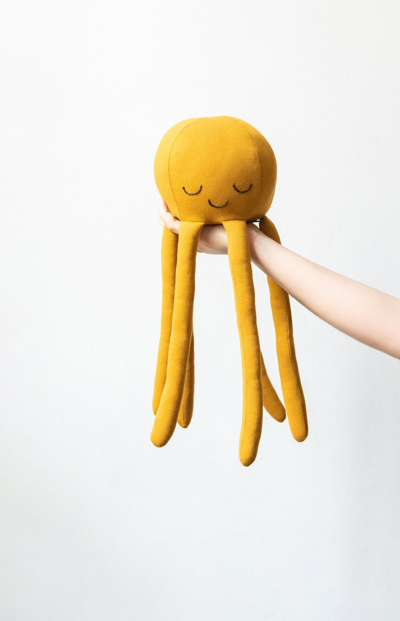 octopus-shaped plush in mustard yellow or gold jersey fabric image 0