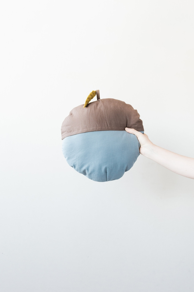decorative cushion in the shape of an acorn with leaf