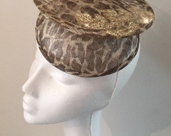 A leopard print sinamay handmade fascinator with gold embellishment