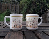 Pair of vintage arcopal coffee mugs. Spots and stripes pattern in pink yellow and green. Milk glass, Opalware. Made in France
