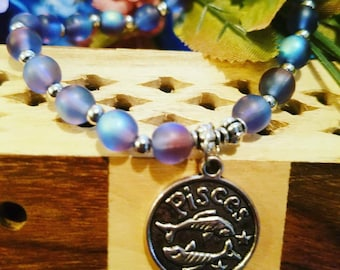 """Pisces zodiac beaded bracelet with """"intuitive"""" stamped on the back of the charm."""