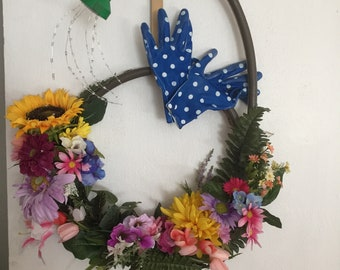 "Spring Floral Wreath on a garden hose with 'water spray""  and garden gloves."
