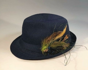 b5e87a95a30 Navy Fedora with amazing Pheasant feather plumb. This hat is sure to be  noticed. The perfect topper for any blazer as you enjoy race day.