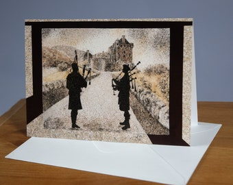 """Greeting card, Reproduction of the sand painting """"Eilean Donan castle in Scotland with bagpipers"""""""
