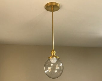 Penelope Gold Raw Brass Modern Chandelier Mid Century Industrial Modern 6 Inch Clear Globe Single Hanging Light