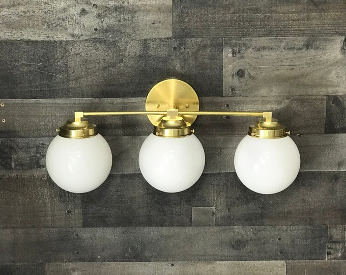 Calliope Raw Brass Gold Modern Sconce Vanity 3 Bulb Clear 6 Inch Globe Abstract Mid Century Art Light Bathroom UL Listed