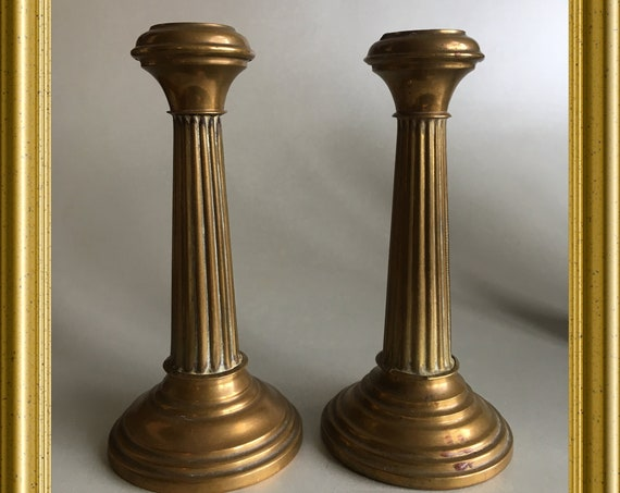 Two small antique brass candle holders