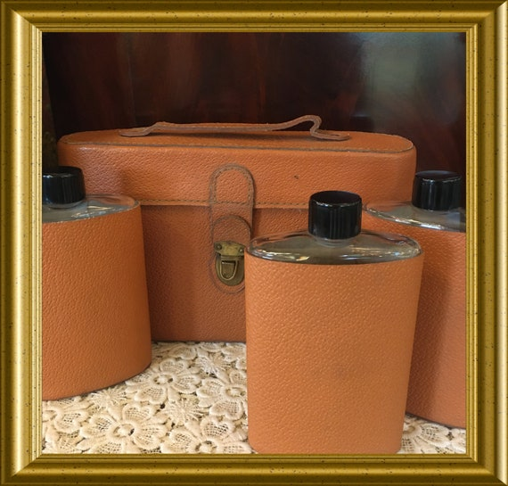 Three vintage flasks/ bottles in leather carrier