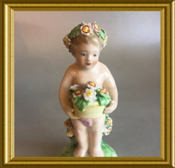Antique porcelain figurine: putto with flowers