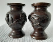Antique, Japanese Meiji period pair of bronze vases decorated in high relief with birds and flowers Circa 1890-1910.