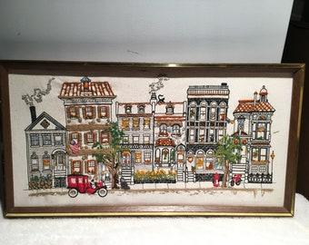 Framed embroidered village scene