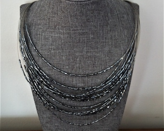 PER UNA Set, Multi-Strand Illusion Crystal Necklace and Bracelet Set; Gunmetal Grey; Sparkling, Movable Tubular Beads; New, Never Used