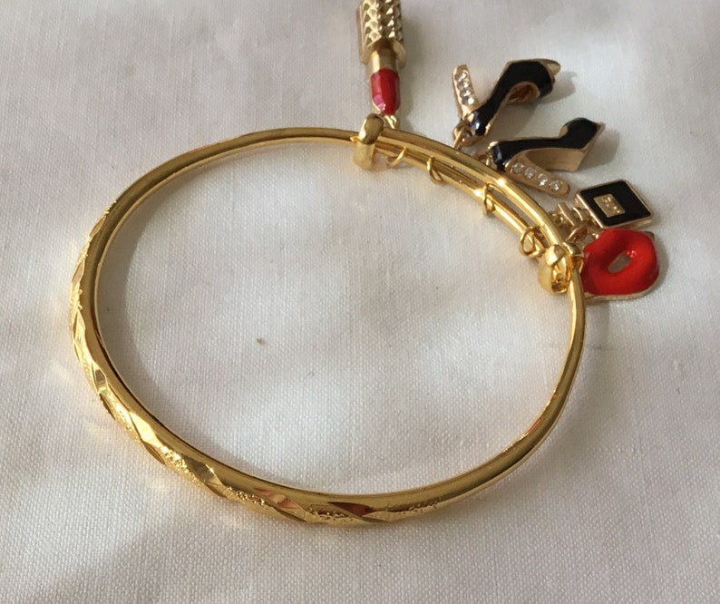 Frankly female 18 karat gold heavily plated stainless steel bangle bracelet with decorative carvings.