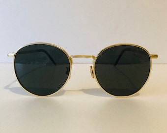 a85dc910d Round metal sunglasses. Gold metal frame and black earpiece; dark lens.  Retro. Vintage sunglasses.
