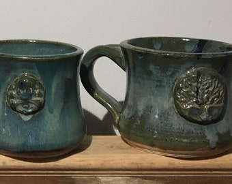 Assortment of Handmade Pottery Mugs with Crystal Glass Glazing and Sculpted Emblem