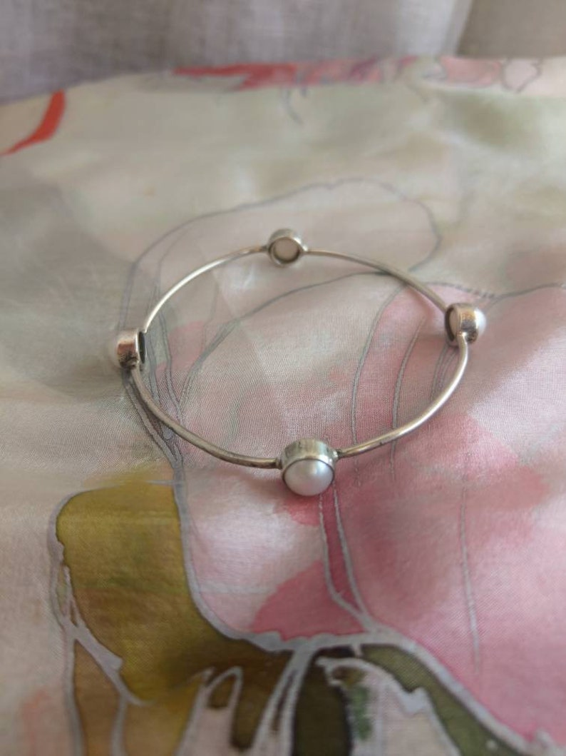 Silver bangle bracelet with four white pearls