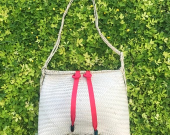 Handwoven rattan shoulder bag with red ribbons