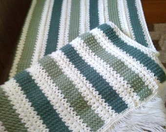 shades of green with white afghan in stripes