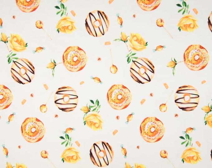 Witte tricot stof met donuts. Gele donuts