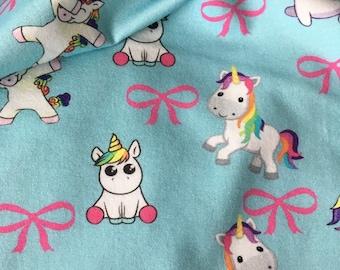 Blauwe tricot stof met eenhoorns. Unicorn stof