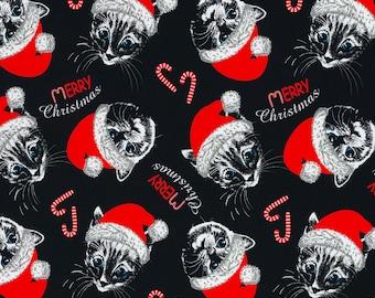 Zwarte tricot stof met katten met kerstmutsen