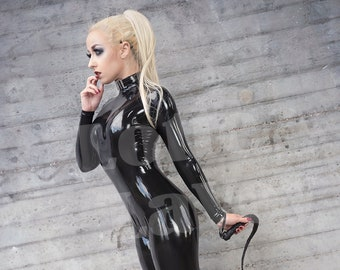 Photo print of model Lotte LaVey in black latex catsuit with whip