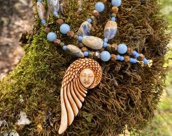 Eagle head & feathers wrapped around peaceful face caved in (ethically sourced) Water Buffalo Bone. Hung from strand of Chalcedony....