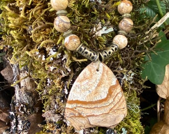 A large pendant of beautiful Picture Jasper hung from a brown leather cord with Picture Jasper beads and brass accents.