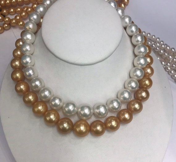 Gold and White Cultured Freshwater Pearls  11.5x15mm is the Gold Strand   11.5x15mm is the White  2 14k Gold Clasps  1 yellow Gold and White