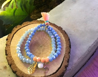 A set of 2 beaded bracelets with pineapple, flamingo charms and tassel.