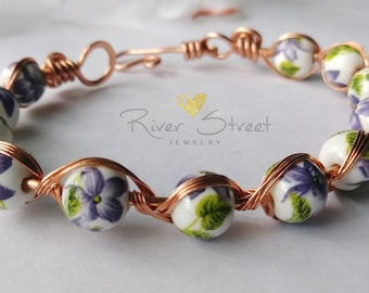 Purple flowers and copper bracelet