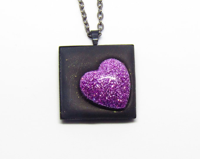 Black square pendant necklace with a lilac glitter heart.