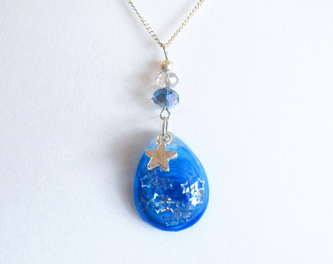 Blue Resin Teardrop Pendant Necklace. Embellished with beads and a star charm. On a silver chain.