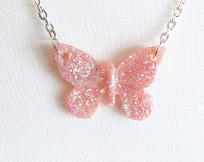 Pink Butterfly Resin Pendant. Sparkly resin pendant on a silver coloured chain.