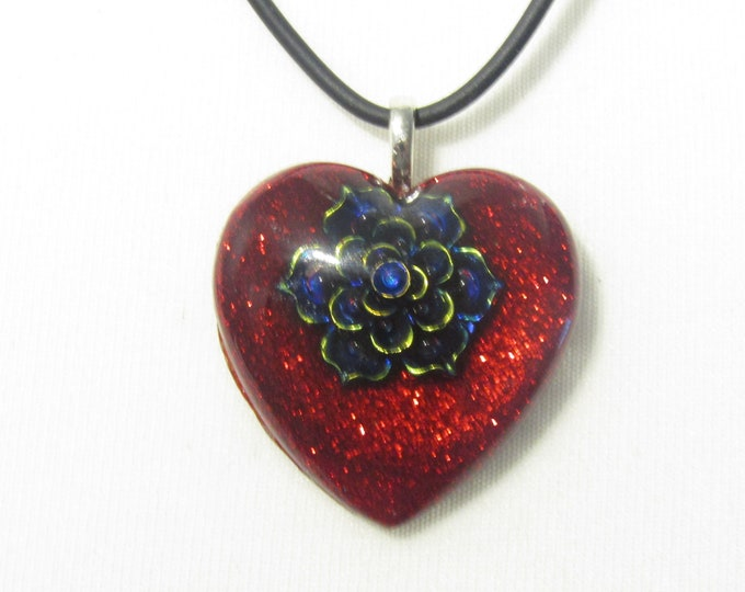 Red Glitter Heart Pendant Necklace. On a black cord. Embellished with an iridescent Flower.
