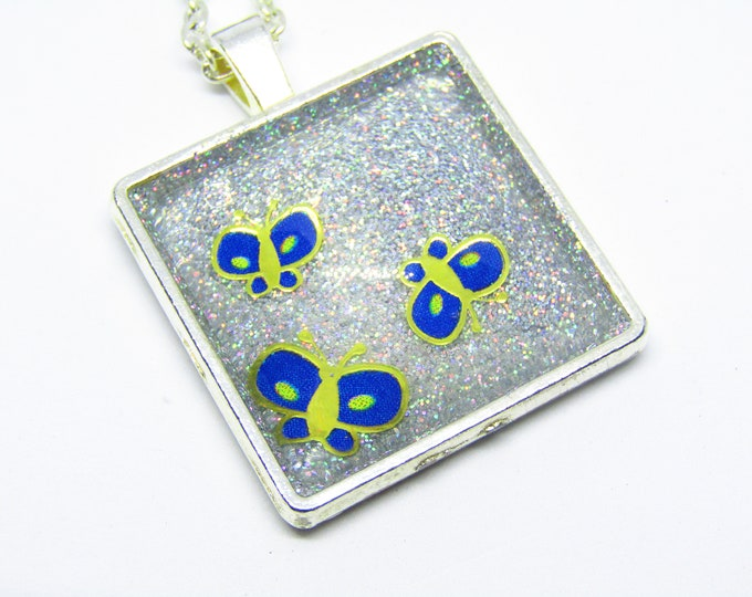 Pretty Butterflies on a Square Pendant Necklace. Blue and gold butterflies on a holographic silver background.