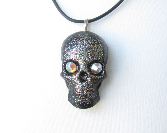 Black and silver skull pendant necklace. Resin pendant on a black cord.