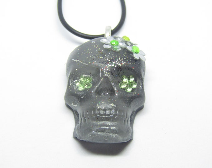 Sugar Skull Resin Pendant Necklace. Grey with silver sparkles and embellished with silver and green flowers. Day of the Dead inspired.