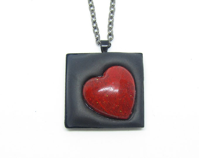 Black square pendant necklace with red heart.