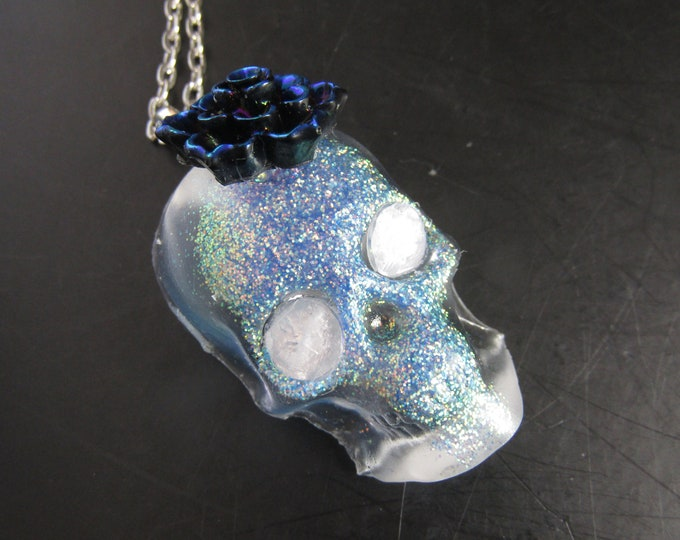 Skull Pendant Necklace. Clear and blue sparkle resin on a silver chain. With iridescent rose embellishment. Day of the Dead inspired.