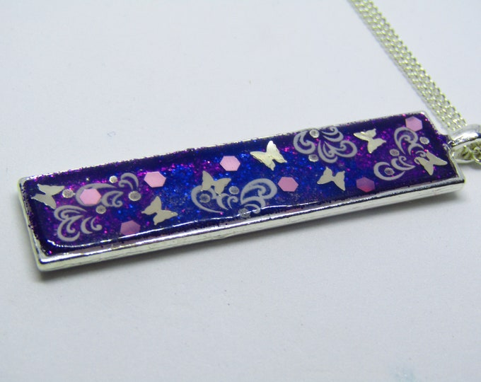 Pretty Rectangular Pendant Necklace. Embellished with Silver Butterflies, pink iridescent spots and white swirls.
