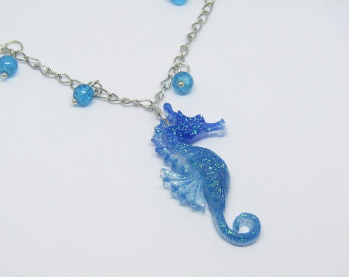 Resin Seahorse Pendant Necklace. On a silver plated chain with turquoise bead embellishment.