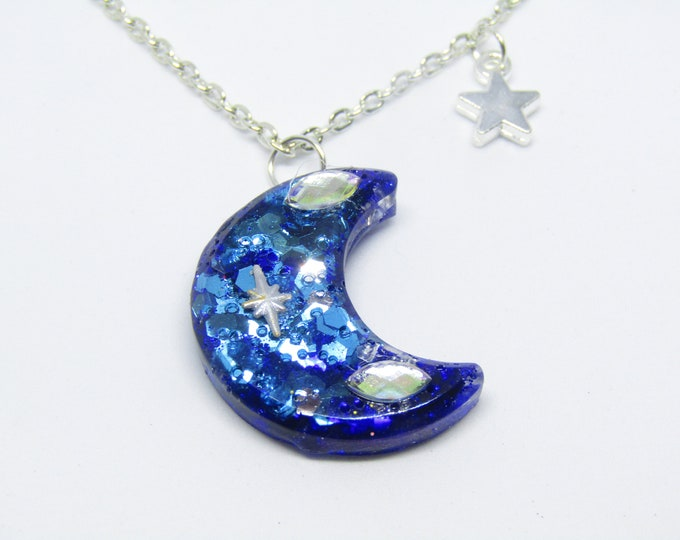 Asymmetrical Blue Glitter Resin Moon Pendant Necklace, with three silver star charms.