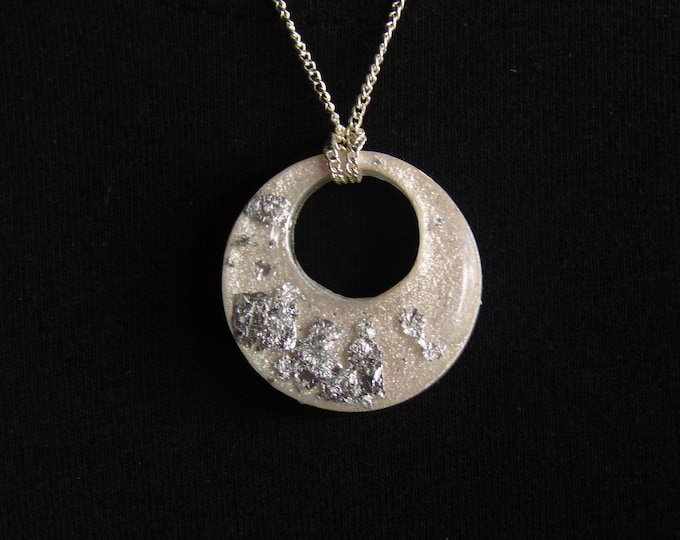 Silvery-white hoop resin pendant necklace with silver foil embellishment.